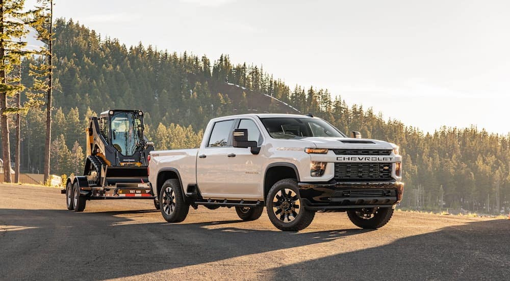 A white 2020 Chevy Silverado 2500HD is towing heavy equipment in the mountains.