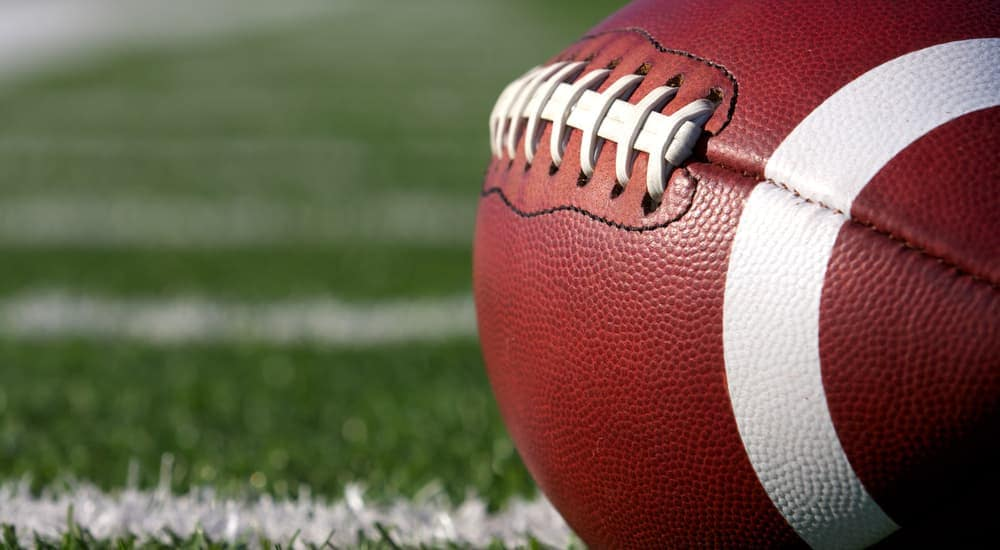 A closeup of a football on the field is shown.