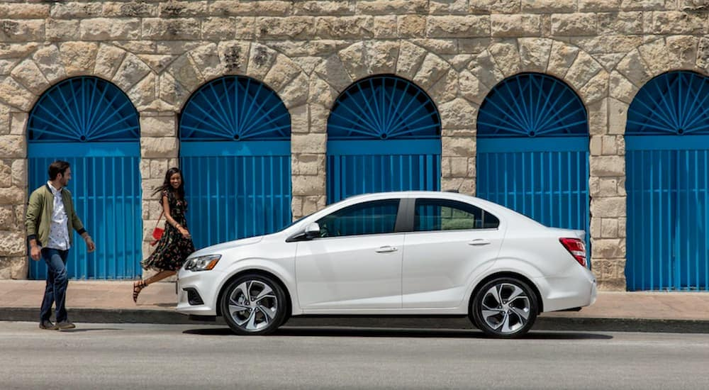 A couple is walking to their white 2019 Chevy Sonic in front of a stone building.