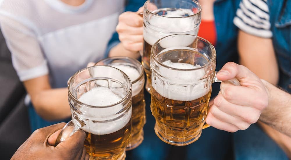 A group of friends hands are holding beer in large glass mugs.