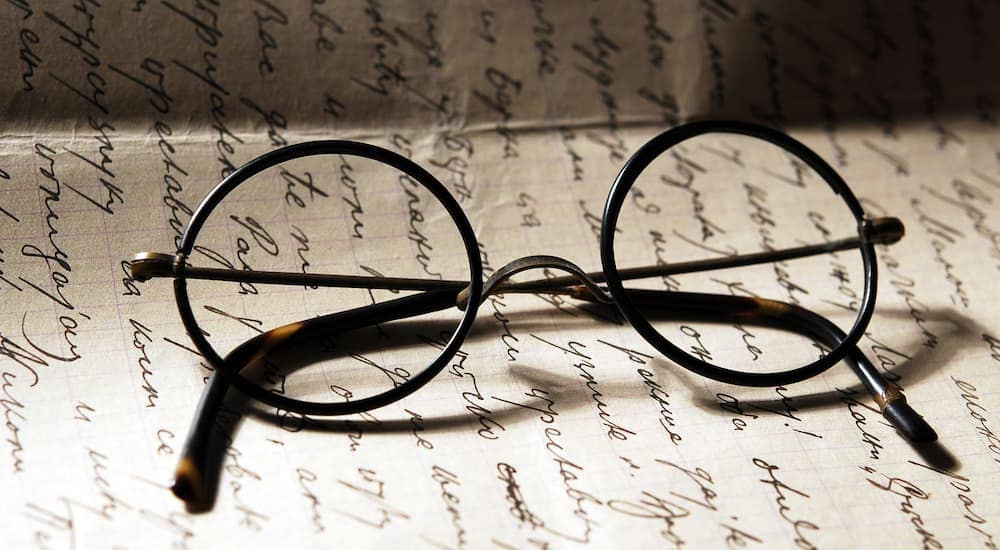 A pair of round rimmed glasses, similar to Harry Potter's glasses, on a paper letter.