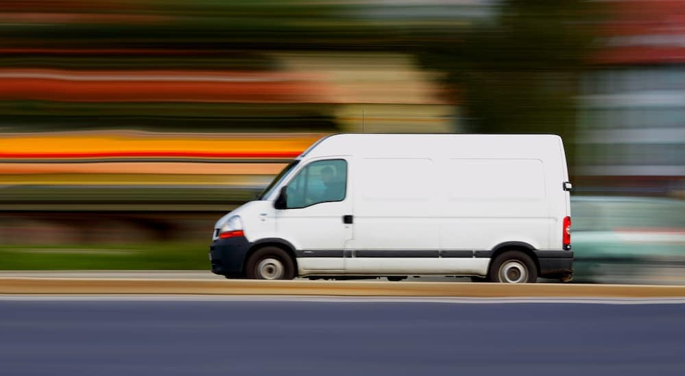 A white van, one of many popular commercial vehicles, is driving down the street in Cincinnati, OH.