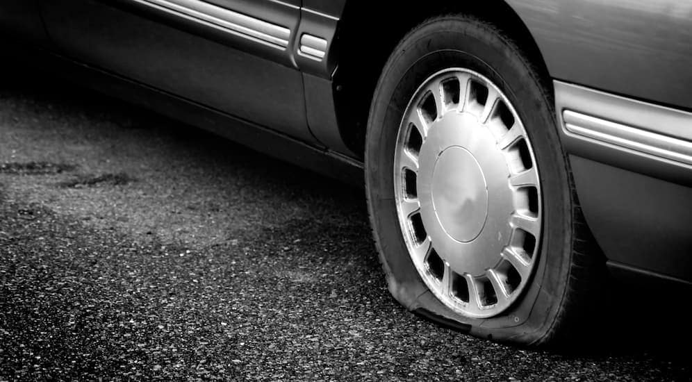 A popped tire on a car is shown. You can avoid this by searching 'best discount tires in Cincinnati'.