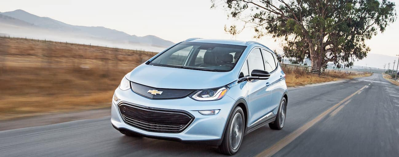 A light blue 2017 Chevy Bolt EV, which wins when comparing the 2017 Chevy Bolt vs 2017 Nissan Leaf, is driving down a road outside of Cincinnati, OH.