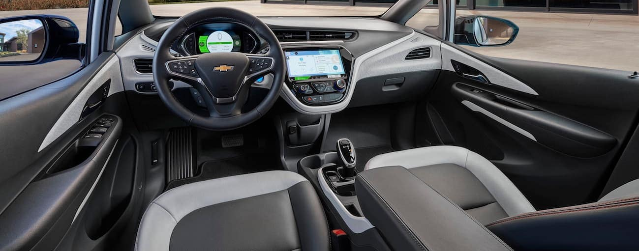 A close up of the front black and white interior in the 2017 Chevy Bolt EV is shown with a touchscreen.
