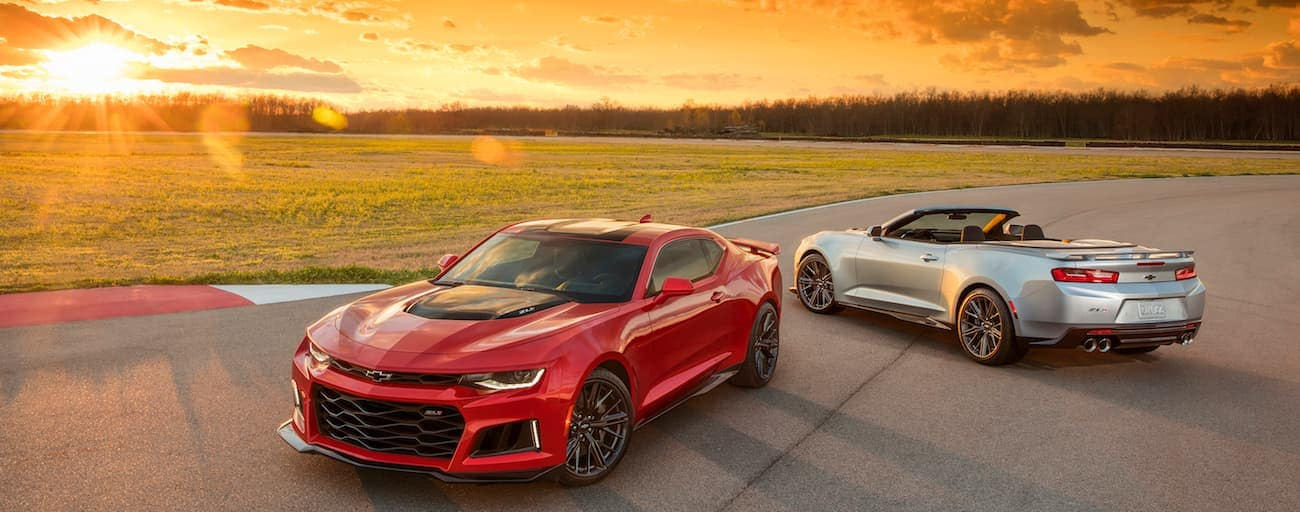 A red and a silver 2017 Chevy Camaro's, which wins when comparing the 2017 Chevy Camaro vs the 2017 Dodge Challenger, are both parked on a racetrack near Cincinnati, OH.