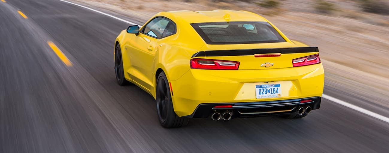 A yellow 2017 Chevy Camaro is racing down a highway in a desert.
