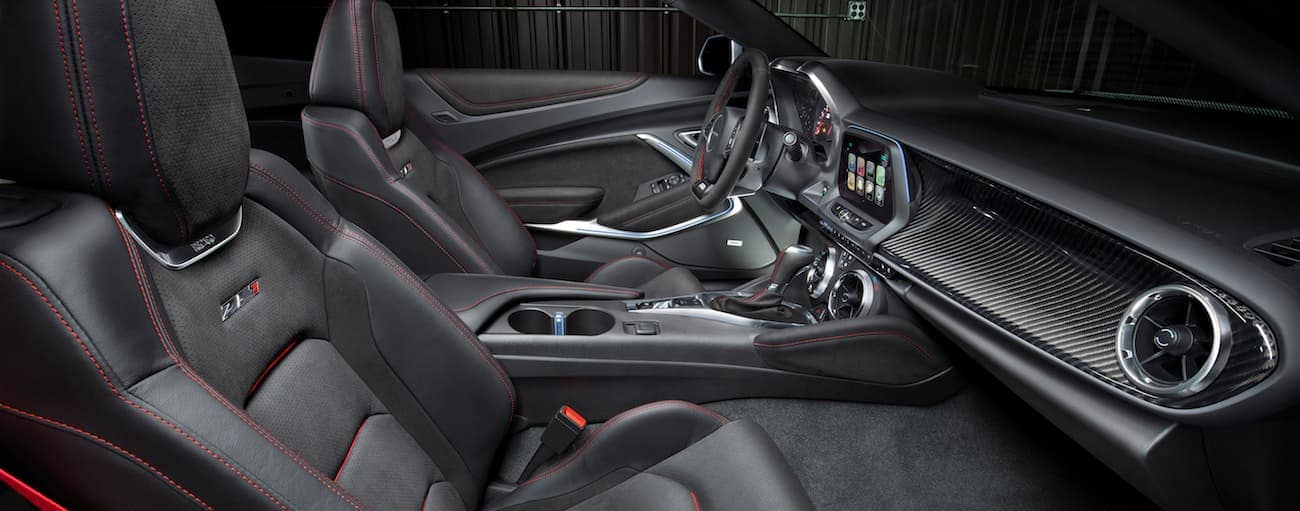 A close up of the front interior of a ZL1 2017 Chevy Camaro is shown with black and red leather.