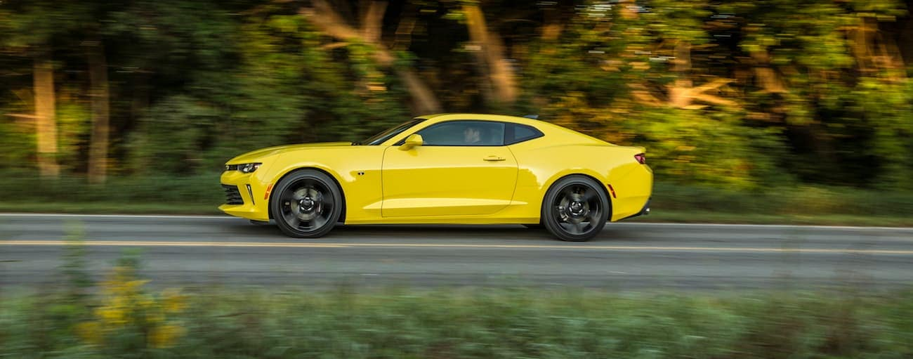 A yellow 2017 Chevy Camaro, which wins when comparing the 2017 Chevy Camaro vs 2017 Ford Mustang, is driving down a road near Cincinnati, OH.