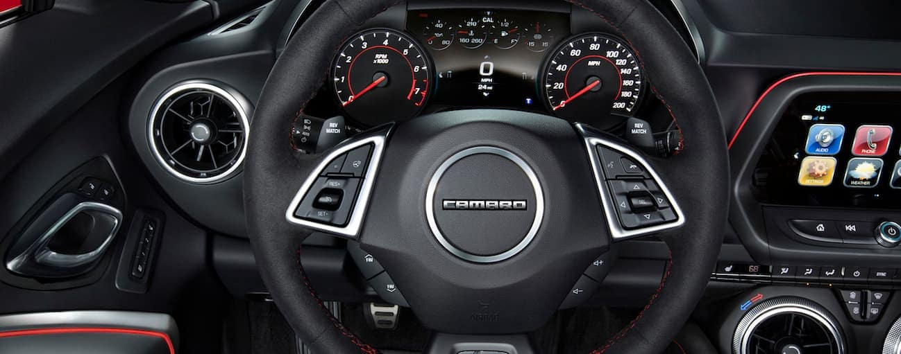 A drivers look at the front of the 2017 Chevy Camaro black leather interior with a touchscreen.
