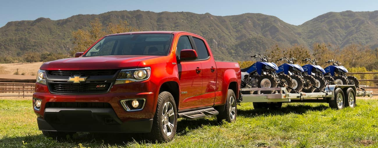 A red 2017 Chevy Colorado, which wins when comparing the 2017 Chevy Colorado vs 2017 Toyota Tacoma, is parked in a field while towing a trailer near Cincinnati, OH.