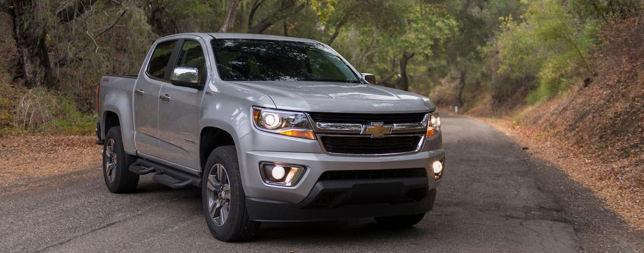 A 2017 silver Chevy Colorado is on a paved road with trees in the background.