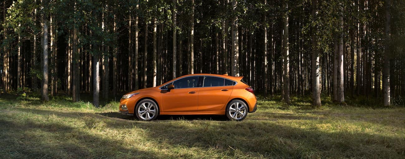 An orange 2017 Chevy Cruze hatchback, which wins when comparing the 2017 Chevy Cruze vs 2017 Ford Focus, is parked on a wooded trail near Cincinnati, OH.