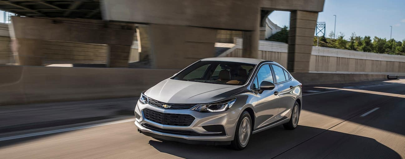 A silver 2017 Chevy Cruze is driving on a highway during the day.