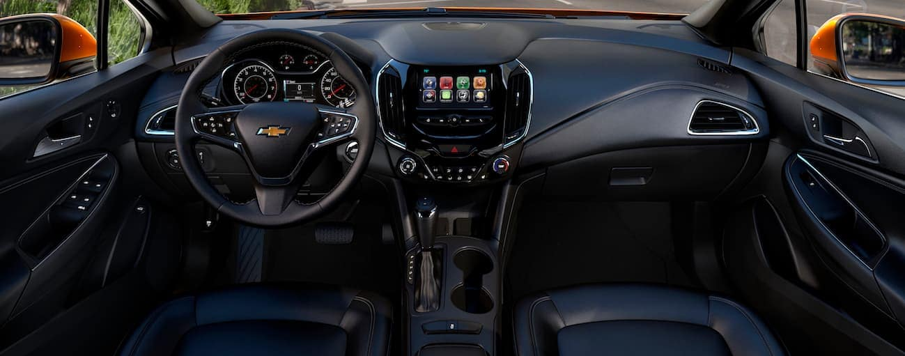 The black leather interior of a 2017 Chevy Cruze is shown with a touchscreen and other high tech features.