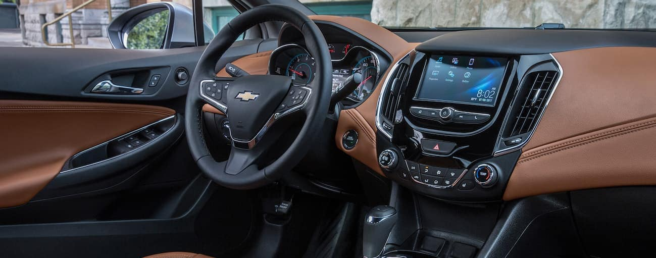 The brown and black leather interior of a 2017 Chevy Cruze is shown with a touchscreen.