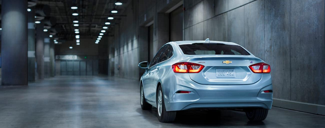 A silver 2017 Chevy Cruze sedan, which wins when comparing the 2017 Chevy Cruze vs 2017 Toyota Corolla, is parked in an empty garage near Cincinnati, OH.