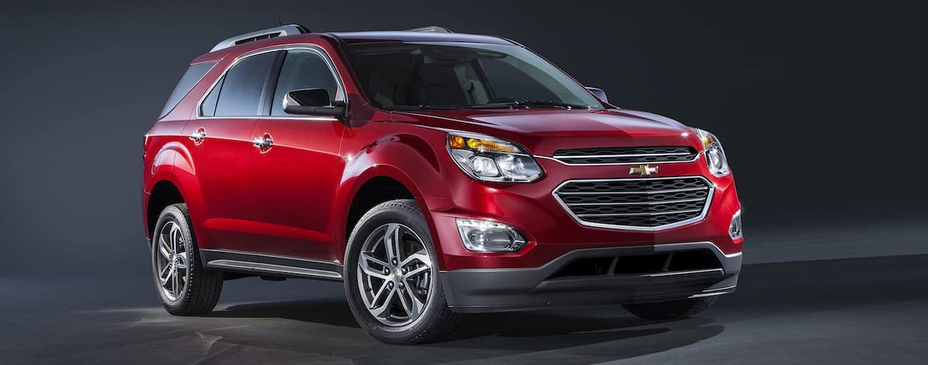 A red 2017 Chevy Equinox is parked in a dark garage.
