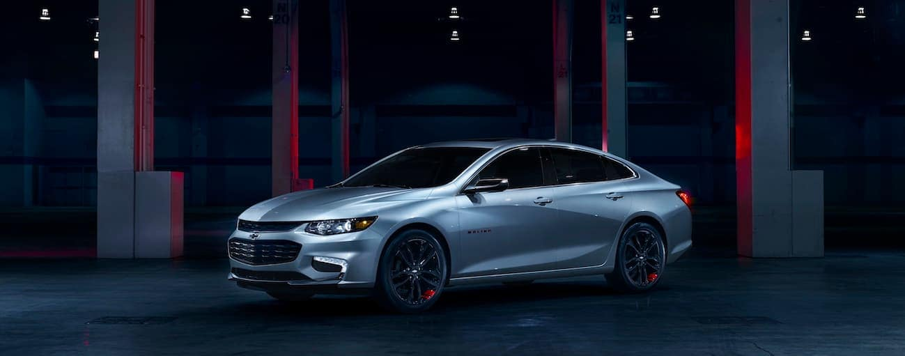 A silver 2017 Chevy Malibu, which wins when comparing the 2017 Chevy Malibu vs 2017 Honda Accord, is parked in a dark garage near Cincinnati, OH.