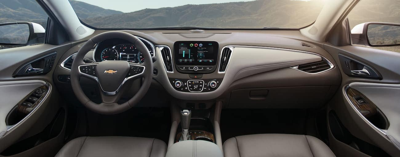The brown and grey interior of a 2017 Chevy Malibu has 6 airbags in the front.