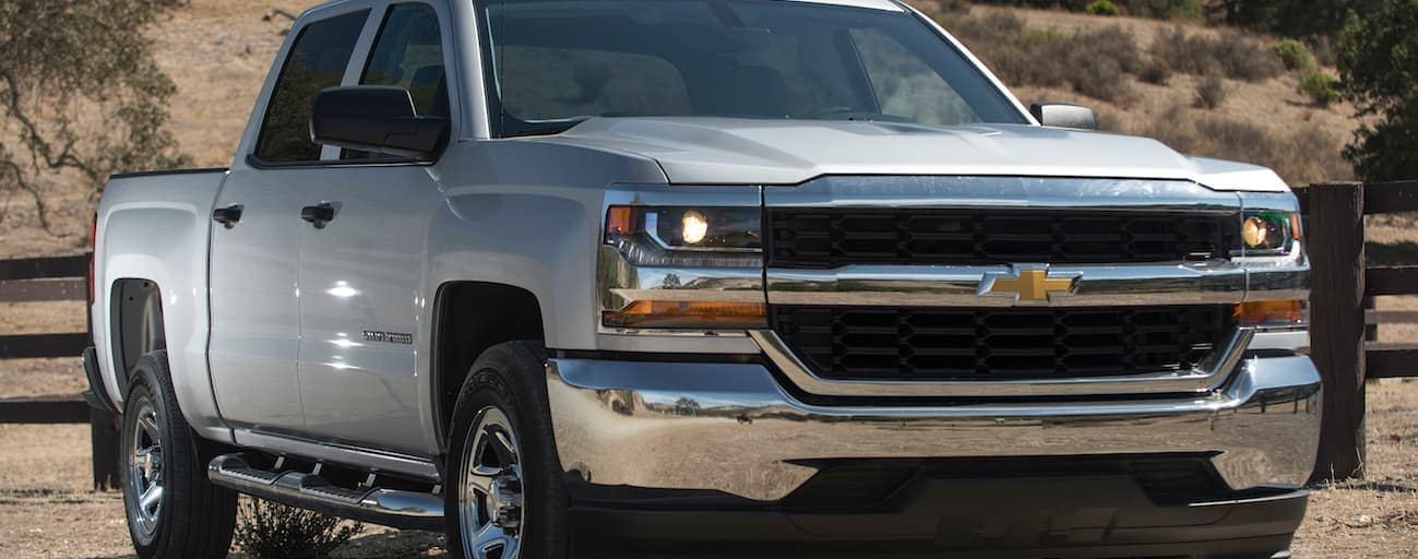 A silver 2017 Chevy Silverado is shown parked on a dirt road.