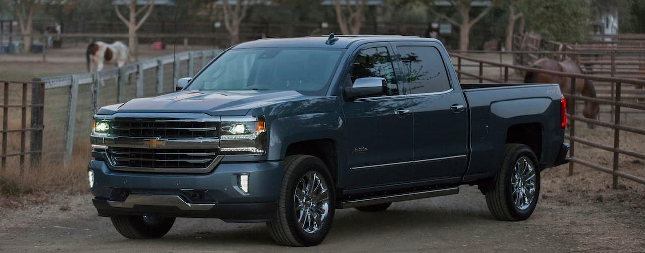A dark blue 2017 Chevy Silverado 1500 is parked in front of a farm.