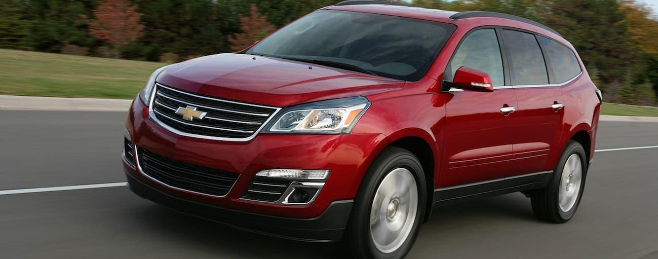 A red 2017 Chevy Traverse is driving down a highway with blurred colored trees behind it.