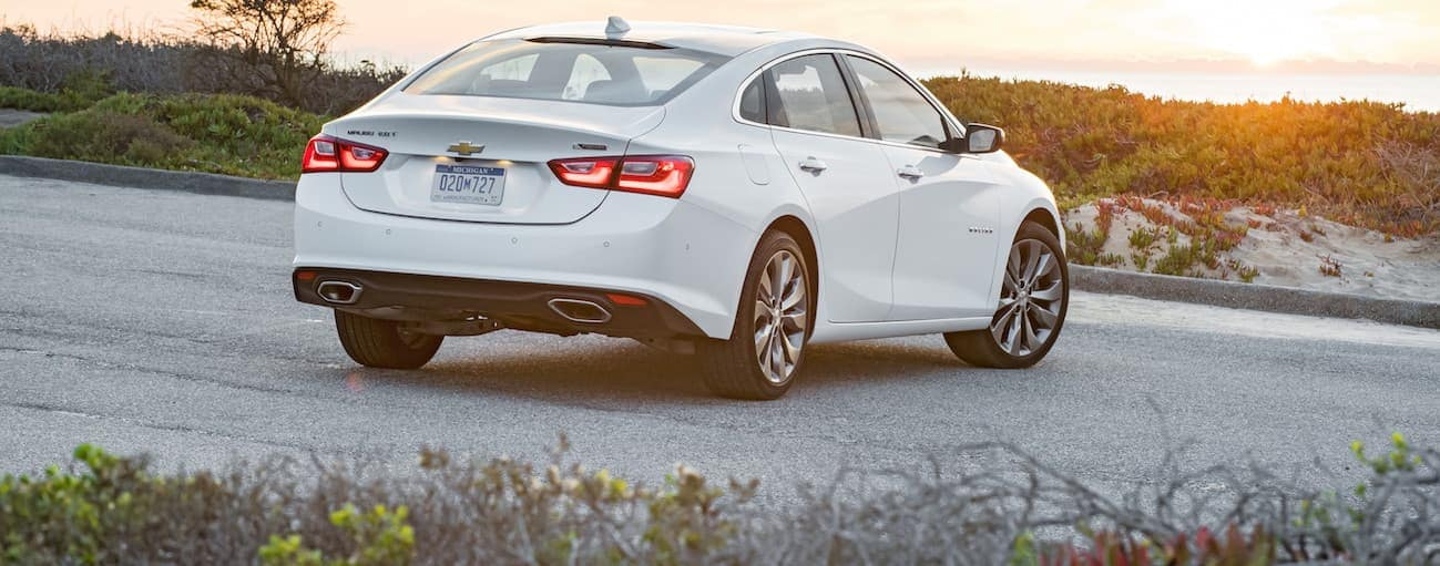 A white 2017 Chevy Malibu is parked on an empty road with a sunset is shown.