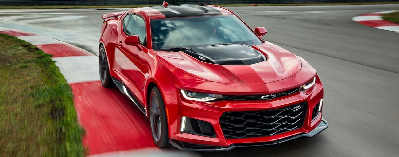 A red, special edition, 2017 Chevy Camaro is driving on a racetrack.
