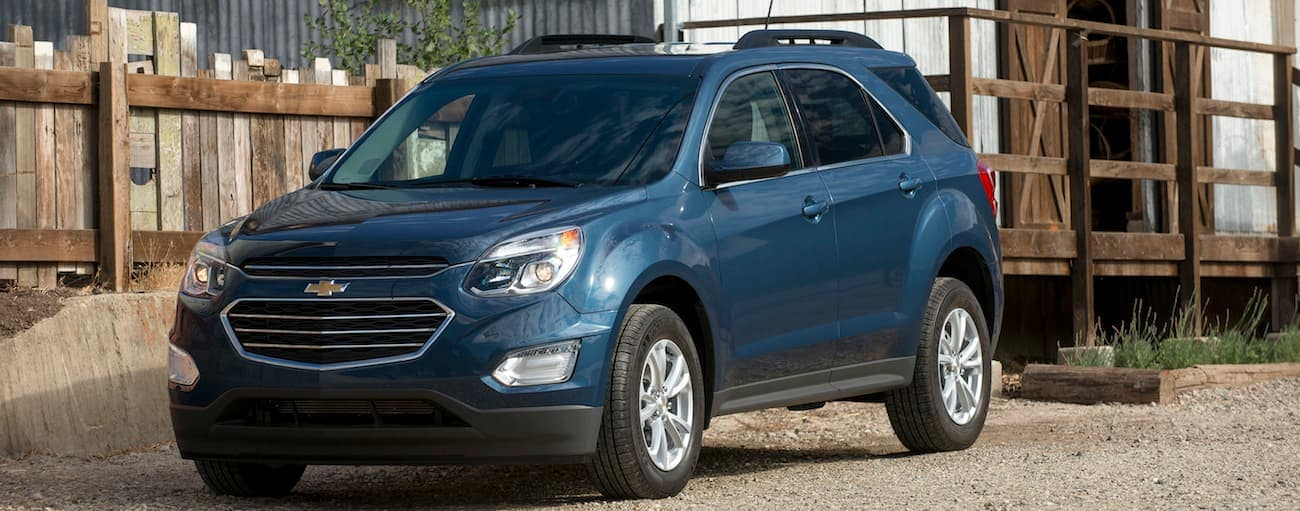 A blue 2017 Chevy Equinox, which wins when comparing the 2017 Chevy Equinox vs 2017 Toyota RAV4, is parked in front of a store outside of Cincinnati, OH.