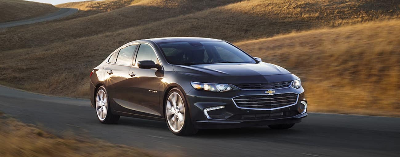 A black 2017 Chevy Malibu is driving by a field.
