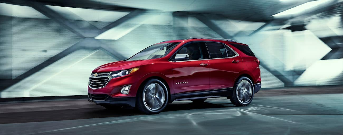 A red 2018 Chevy Equinox, which wins when comparing 2018 Chevrolet Equinox and the 2018 Honda CR-V, is driving on a highway near Cincinnati, OH.