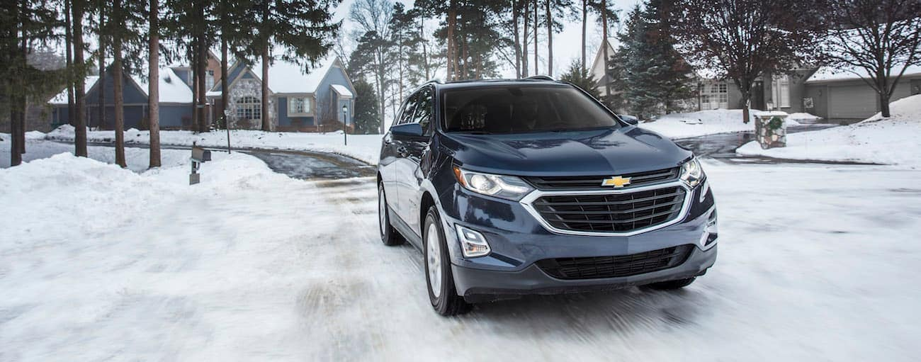 A blue 2018 Chevy Equinox, which wins when comparing the 2018 Chevrolet Equinox vs 2018 Kia Sportage, is driving down a snowy road near Cincinnati, OH.
