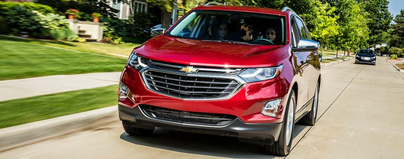 A red 2018 Chevy Equinox, which wins when comparing the 2018 Chevrolet Equinox vs 2018 Ford Escape, is driving down a street near Cincinnati, OH.