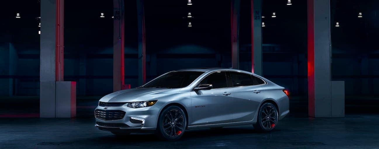 A silver 2018 Chevy Mailbu is parked inside a dark garage.