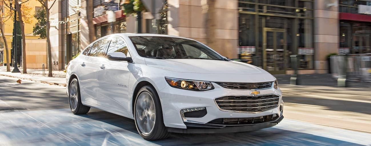 A white 2018 Chevy Malibu, which wins when comparing the 2018 Chevrolet Malibu vs 2018 Kia Optima, driving near Cincinnati, OH.