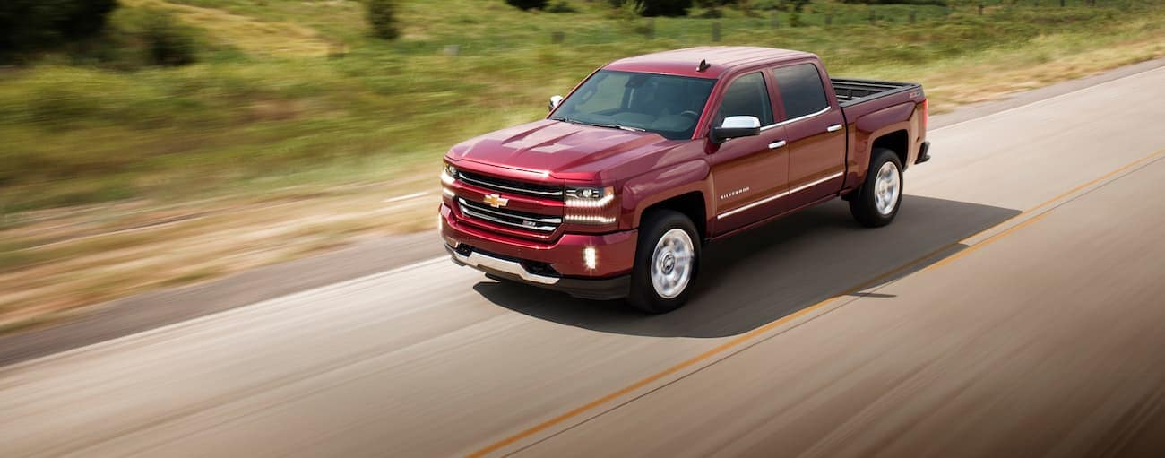 A red 2018 Chevy Silverado, which wins when comparing the 2018 Chevrolet Silverado vs 2018 Ford F-150, is driving down a road near Cincinnati, OH.