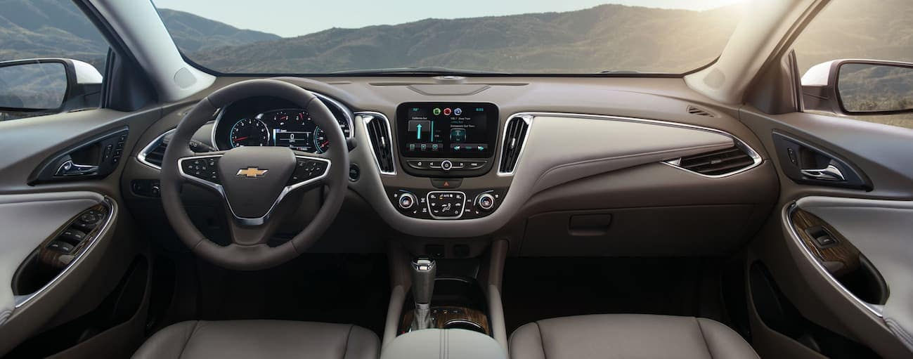 The brown and grey interior of a 2018 Chevy Malibu is shown. with a touchscreen.