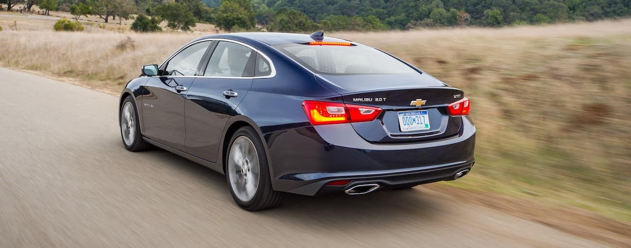 A dark blue 2018 Chevy Malibu, which wins when comparing the 2018 Chevrolet Malibu vs 2018 Nissan Altima, is driving passed a field near Cincinnati, OH.