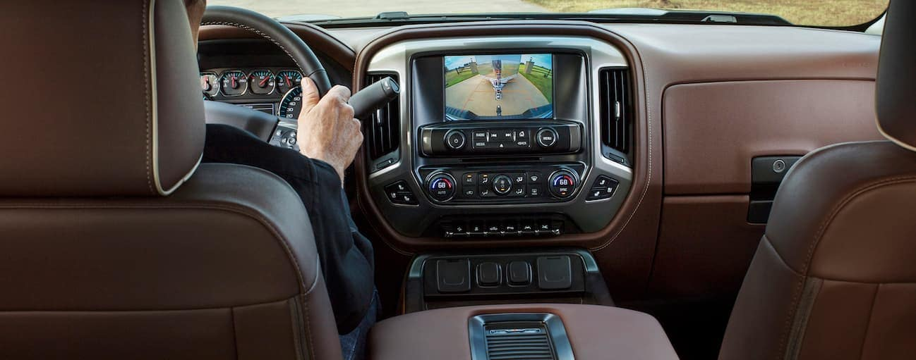 The brown and black leather interior of a 2018 Chevy Silverado 1500 is shown with a touch screen.