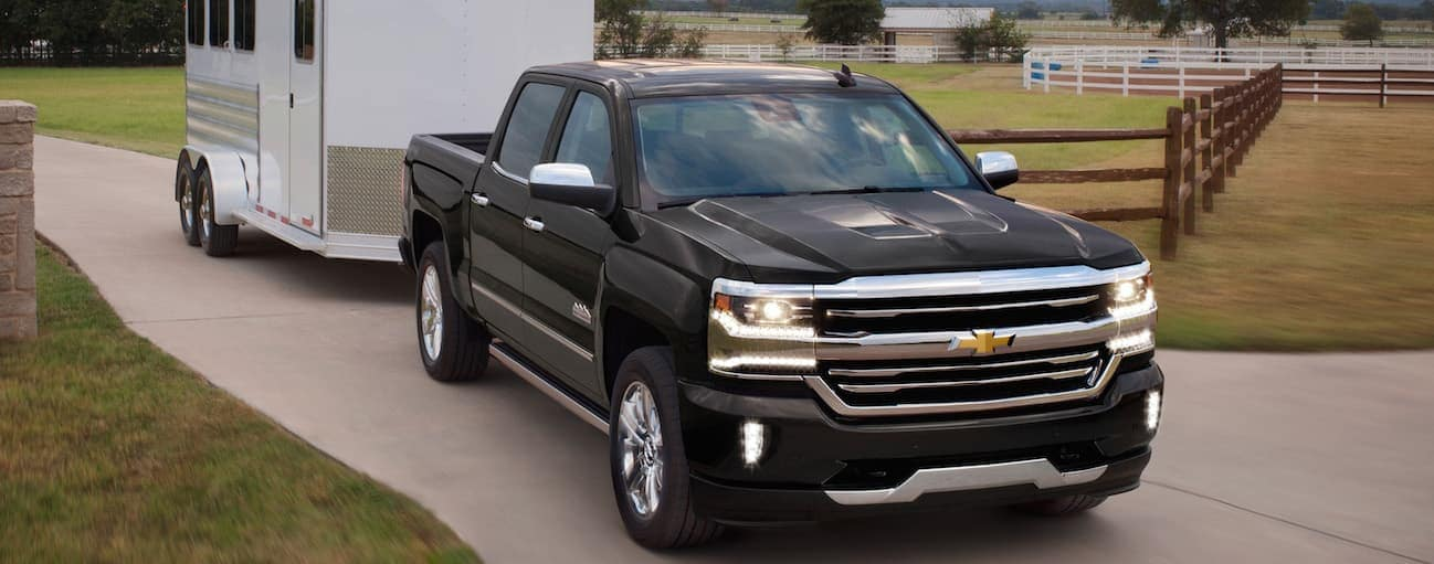 A black 2018 Chevy Silverado is shown pulling a horse trailer.