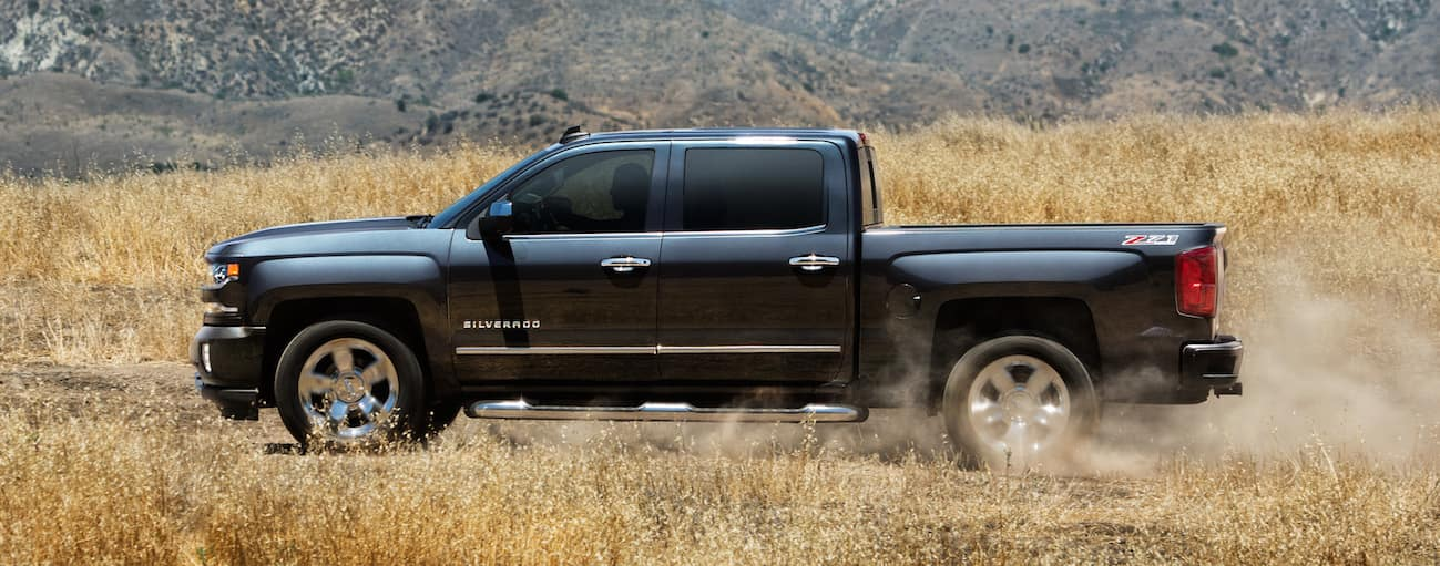 A black 2018 Chevy Silverado is driving past a high field.