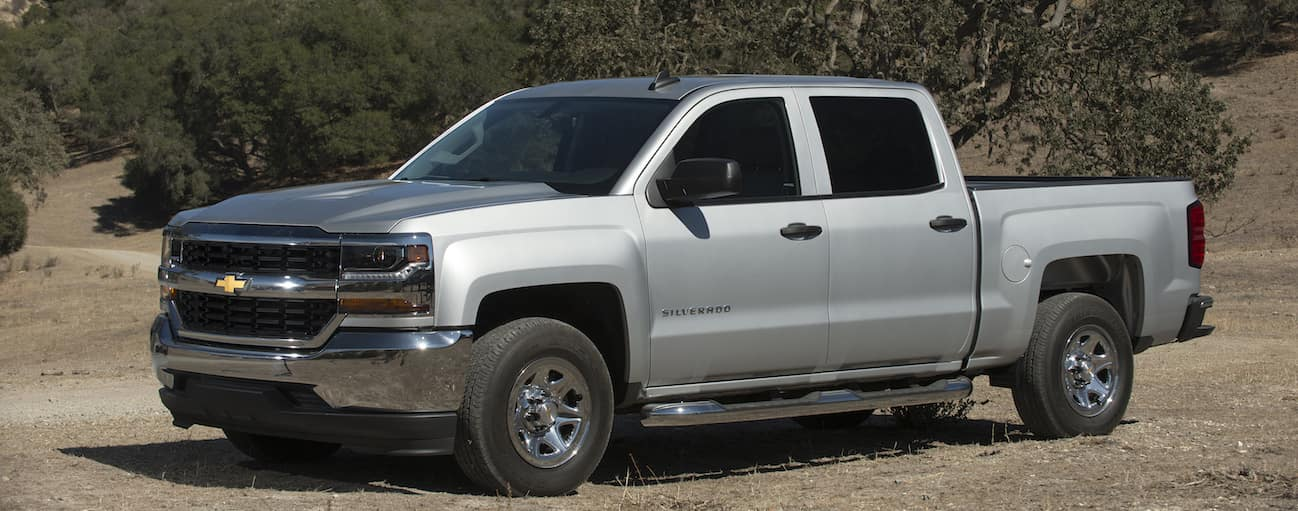 A silver 2018 Chevy Silverado, which wins when comparing the 2018 Chevy Silverado vs 2018 Nissan Titan, is parked in a field near Cincinnati, OH.