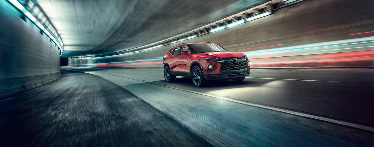 A red 2019 Chevy Blazer, which wins when comparing the 2019 Chevy Blazer vs the 2019 KIA Sorento, is driving through a dark tunnel.