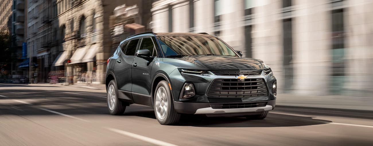 A green 2019 Chevy Blazer, which wins when comparing the 2019 Chevy Blazer vs 2019 Hyundai Santa Fe is driving down a street in Cincinnati, OH.