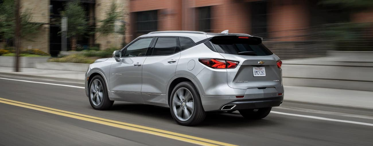 A silver 2019 Chevy Blazer is driving past brick buildings.