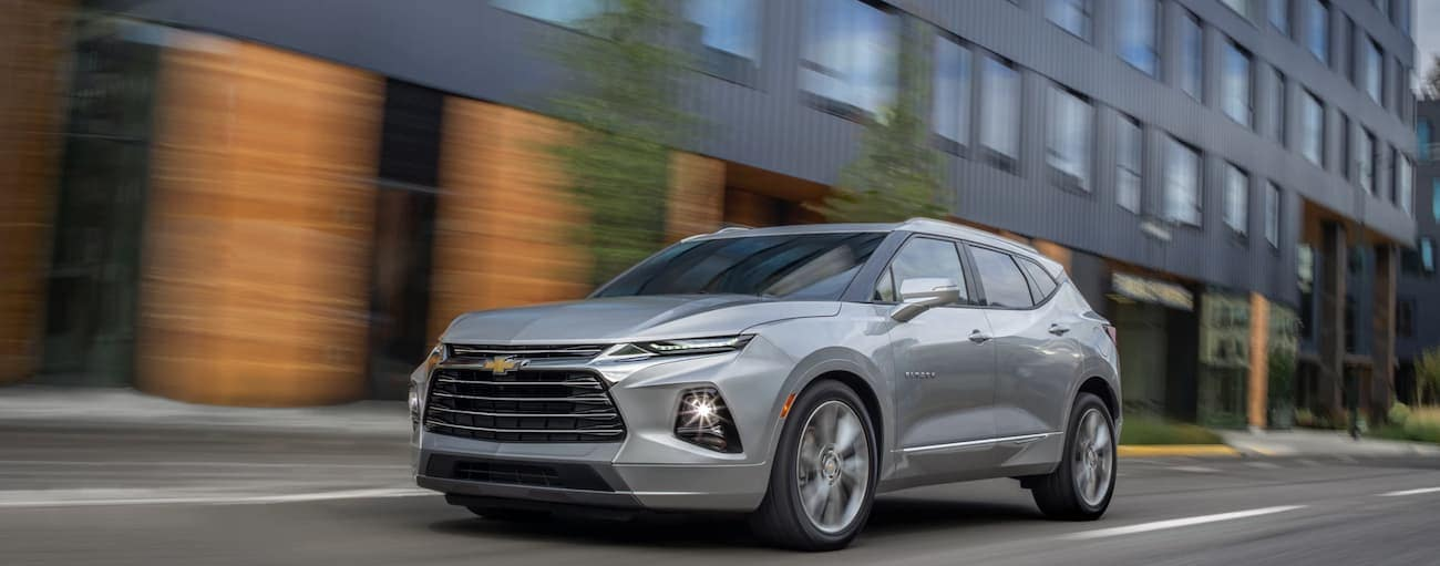 A grey 2019 Chevy Blazer, which wins when comparing the 2019 Chevy Blazer vs 2019 Jeep Cherokee, is driving past a black building near Cincinnati, OH.