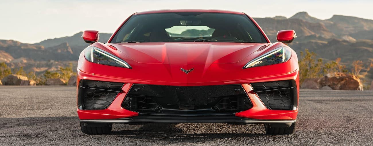 A red 2020 Chevy Corvette 2LT is shown from the front with mountains in the distance.