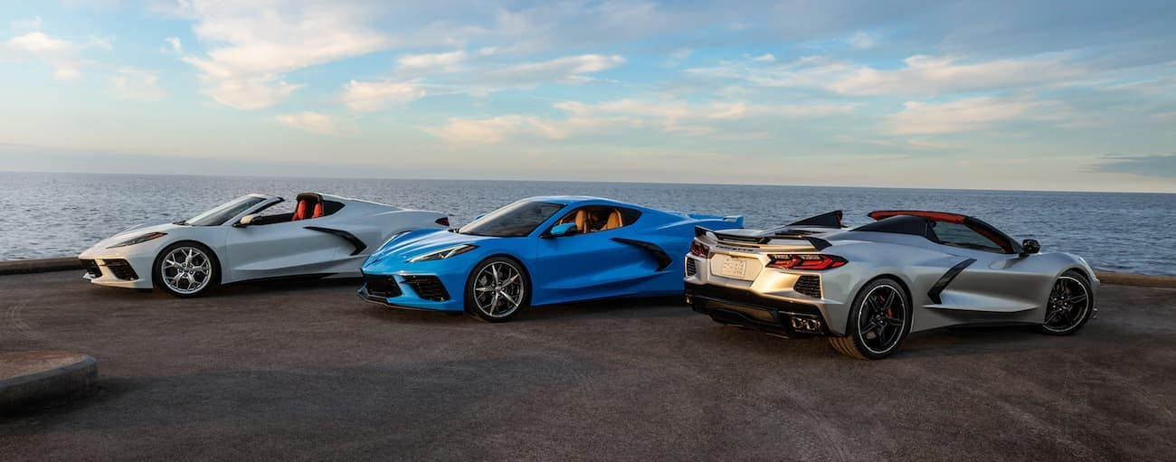 A silver, a blue, and a white 2020 Chevy Corvette are parked on a pier.