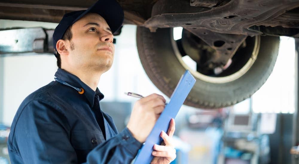 A mechanic holding a clipboard is under a car in a Cincinnati, OH garage.